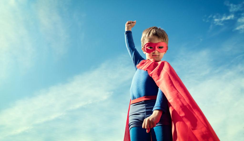 Kleiner Junge im Superhelden-Kostüm.