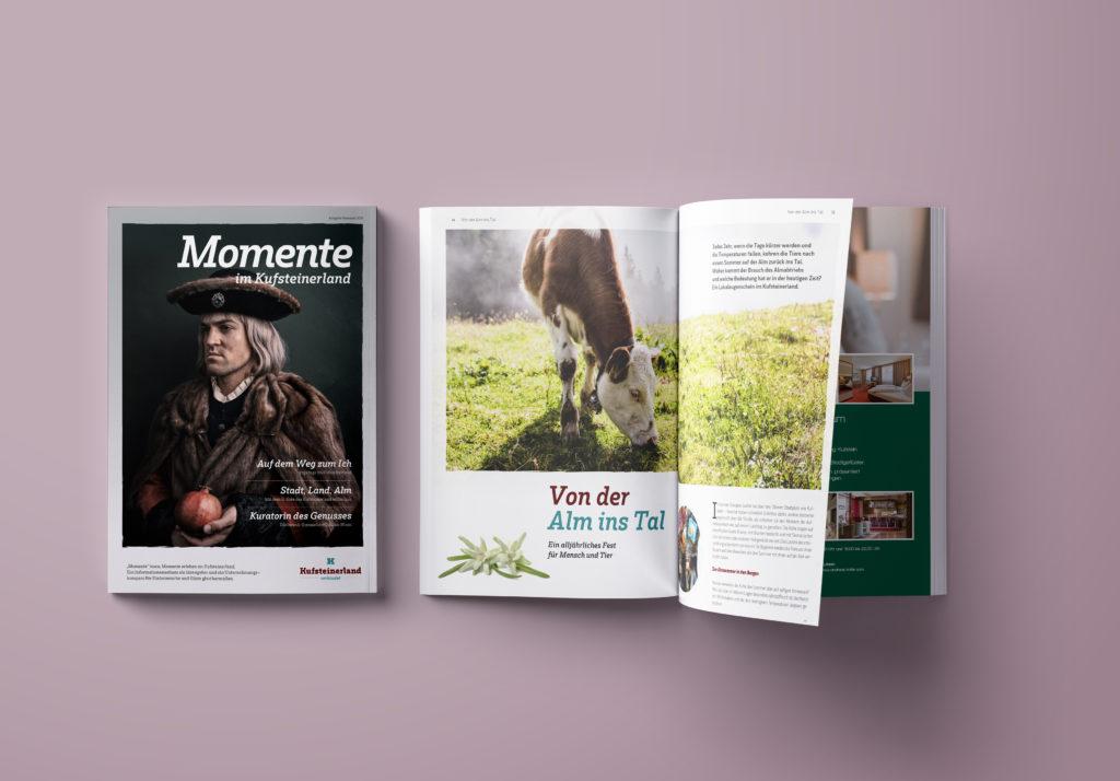 Zwei Momente-Magazine des Tourismusverbandes Kufsteinerland liegen nebeneinander – eines mit dem Cover nach oben und eines aufgeschlagen.