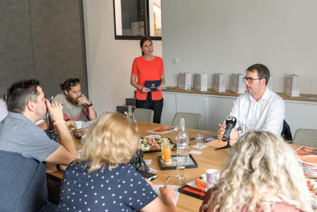 Szenerie eines Pressegesprächs: JournalistInnen sitzen versammelt um einen Tisch, am Mikrofon der Protagonist, im Hintergrund steht die Moderatorin
